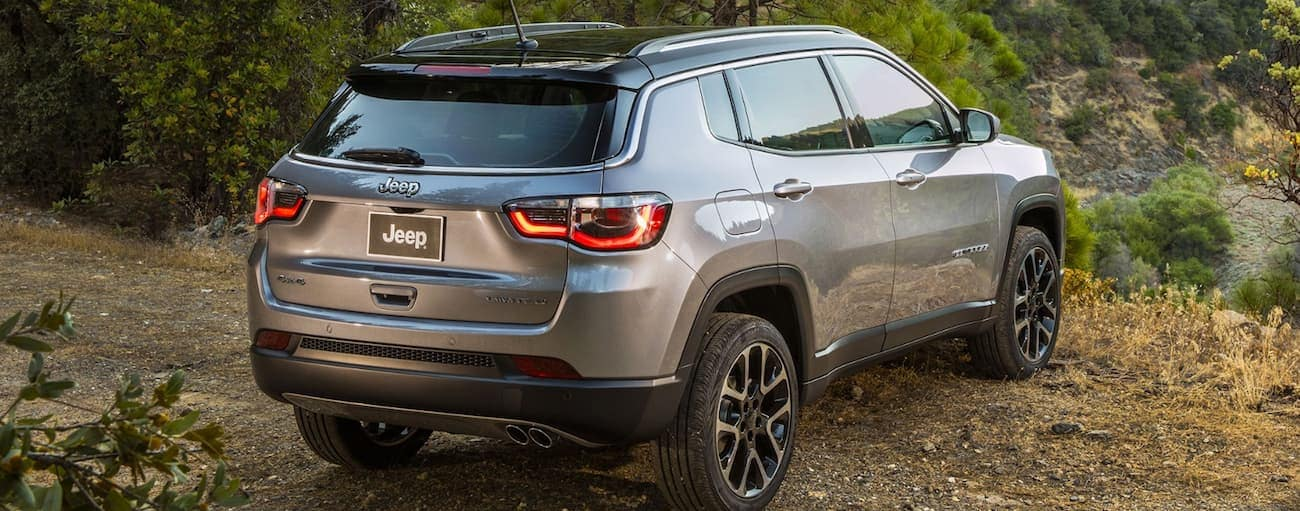 A grey 2020 Jeep Compass is parked on a dirt path that is overlooking a valley near Costa Mesa, CA.