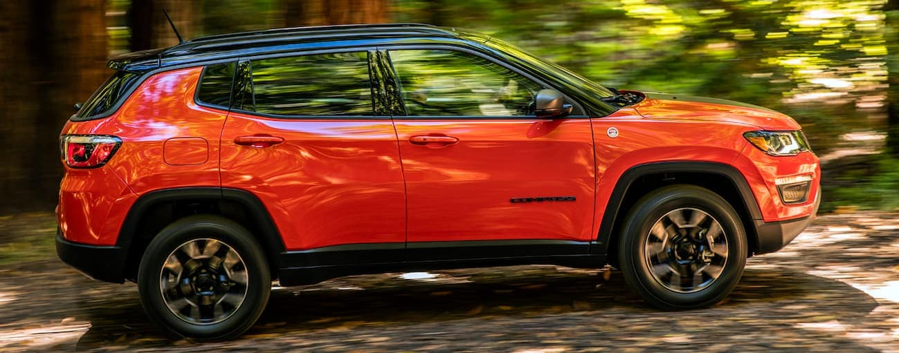 A red 2020 Jeep Compass is driving on a dirt path through the woods near Costa Mesa, CA.