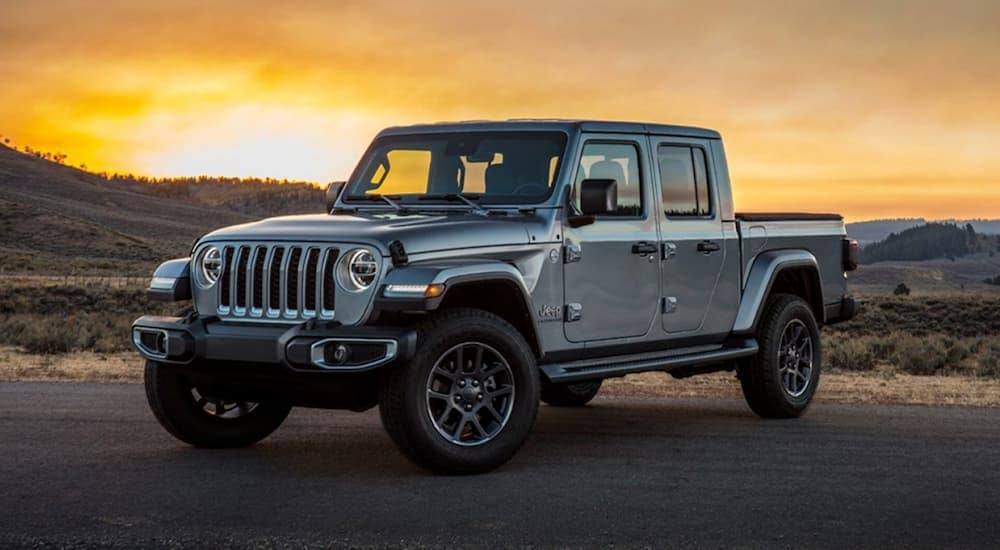 A silver 2020 Jeep Gladiator, which is a new arrival that you could see at your local Costa Mesa, CA Jeep dealership, is parked with a sunset in the distance.
