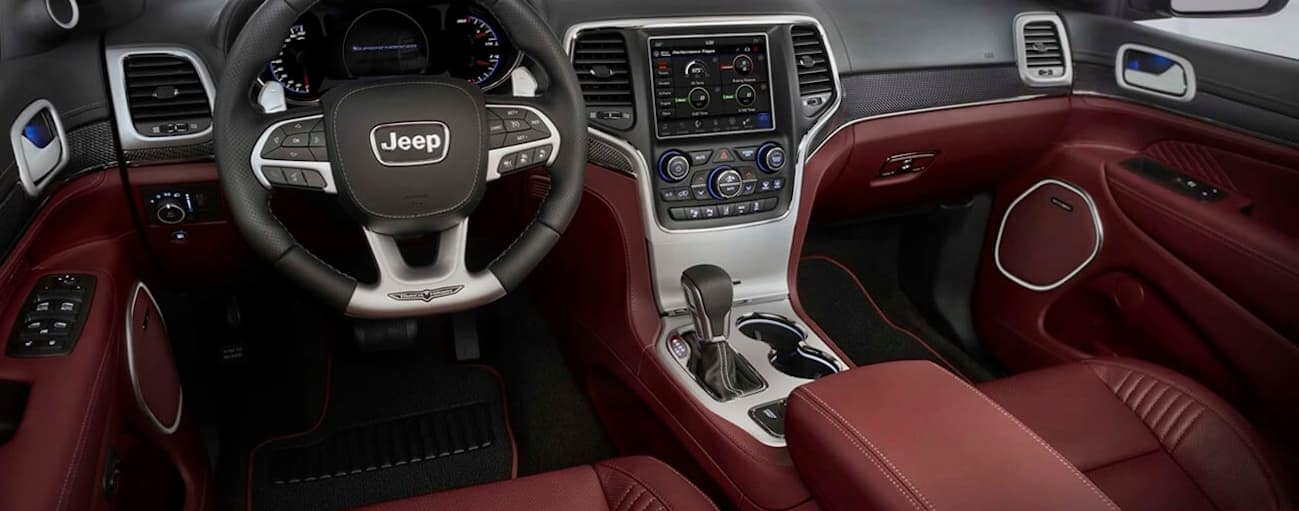 The front luxurious red leather interior of the 2020 Jeep Grand Cherokee is shown.