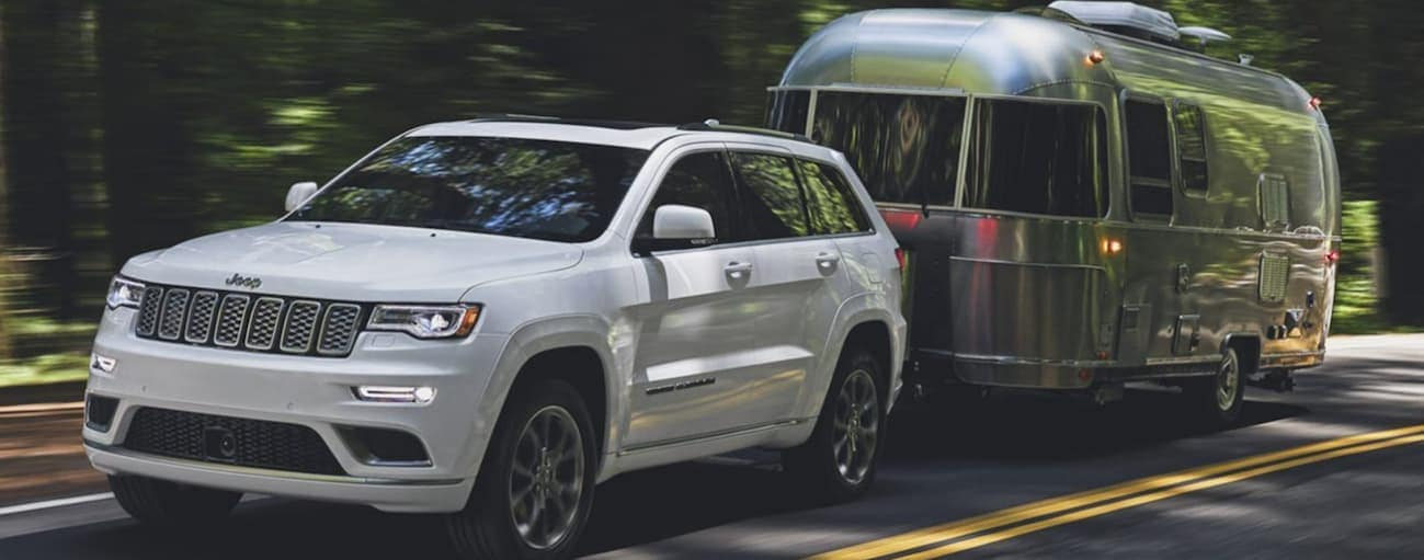 A white 2020 Jeep Grand Cherokee is towing an Airstream on a treelined road.