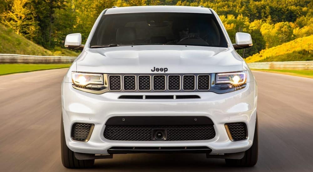 A white 2020 Jeep Grand Cherokee is facing forward while driving on a highway near Costa Mesa, CA.