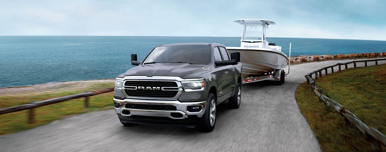 A grey 2020 Ram 1500 is towing a boat near Costa Mesa, CA.