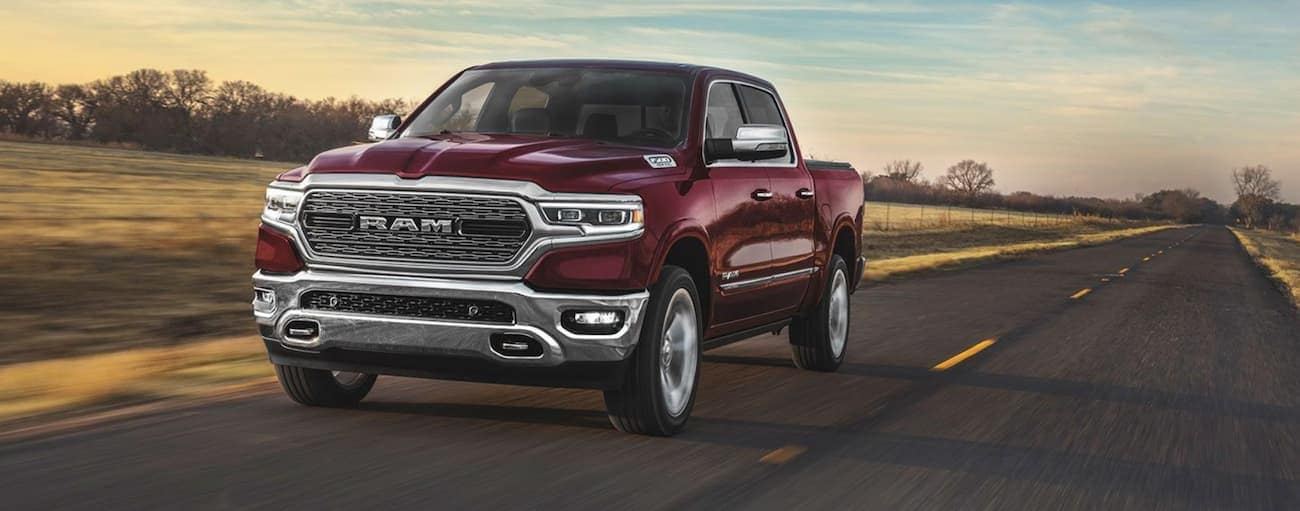 A red 2020 Ram 1500 is driving on a sunny highway.