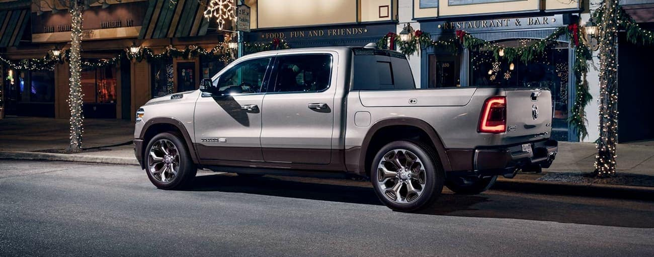 A silver 2020 Ram 1500 is on a city street at night.