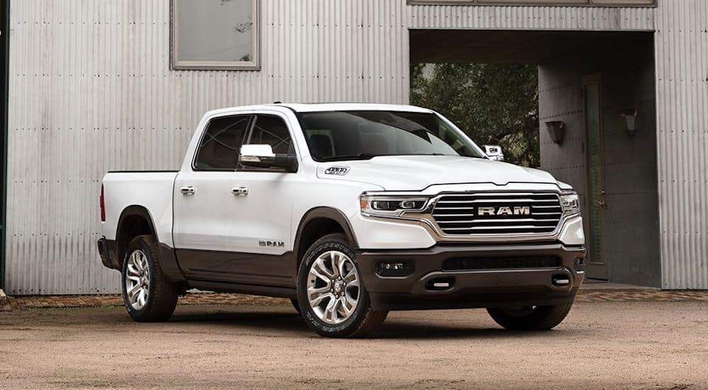 A white 2020 Ram 1500, which is a popular model among the 2020 Ram trucks, is parked in front of a warehouse near Costa Mesa, CA.