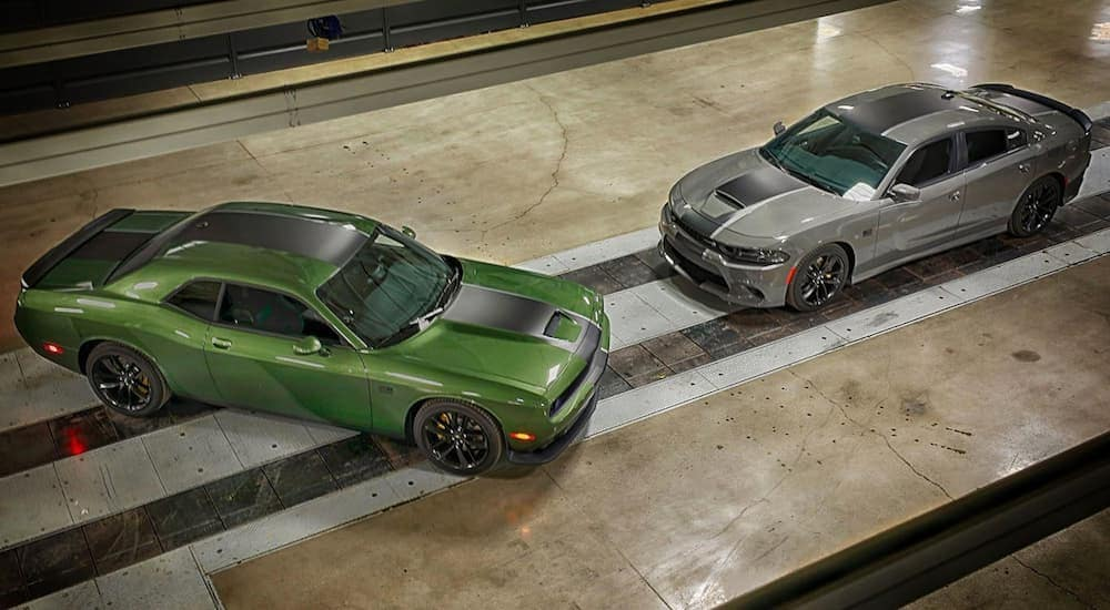 A birds eye view of a 2020 green Challenger and a grey 2020 Charger parked inside of a garage.