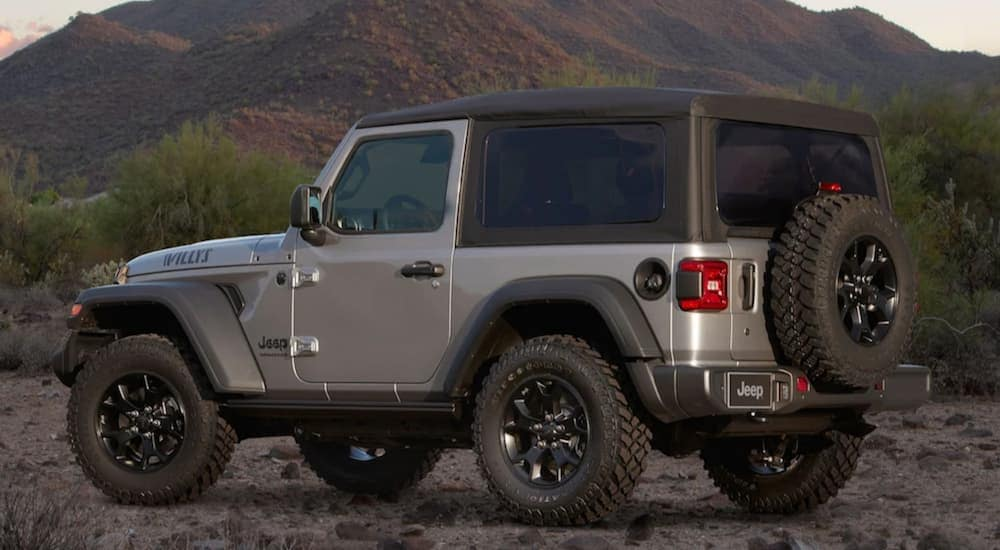 A silver 2020 Jeep Wrangler is parked on a dirt road while facing a large mountain at dusk.