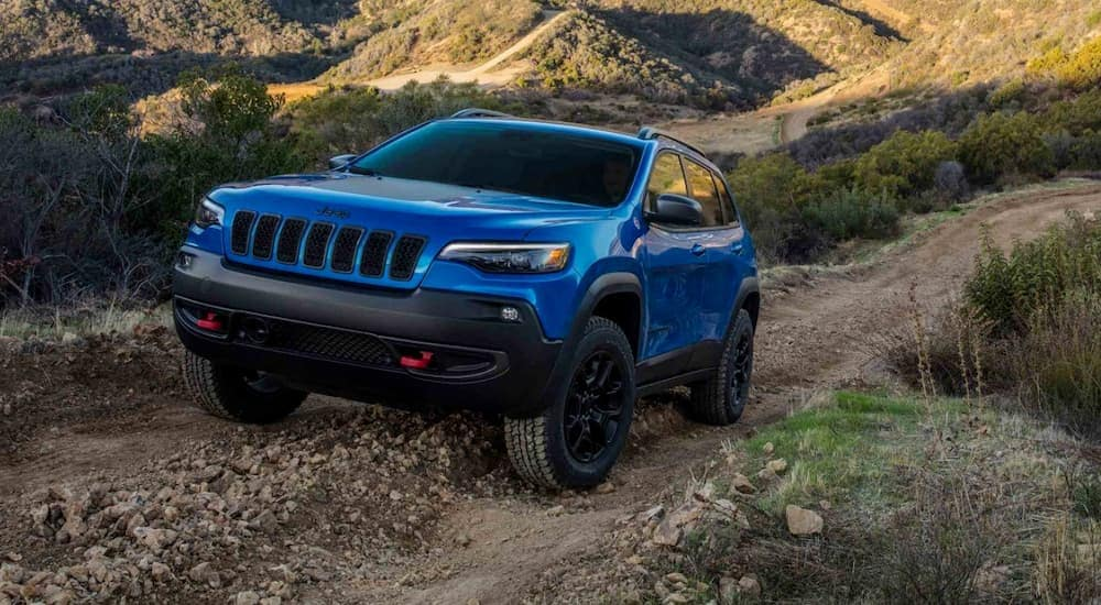 A blue 2019 Jeep Cherokee is driving uphill on a dirt road.