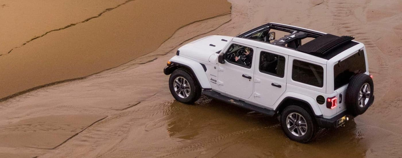 A white 2020 Jeep Wrangler is parked on the beach shoreline after leaving a Jeep dealership.