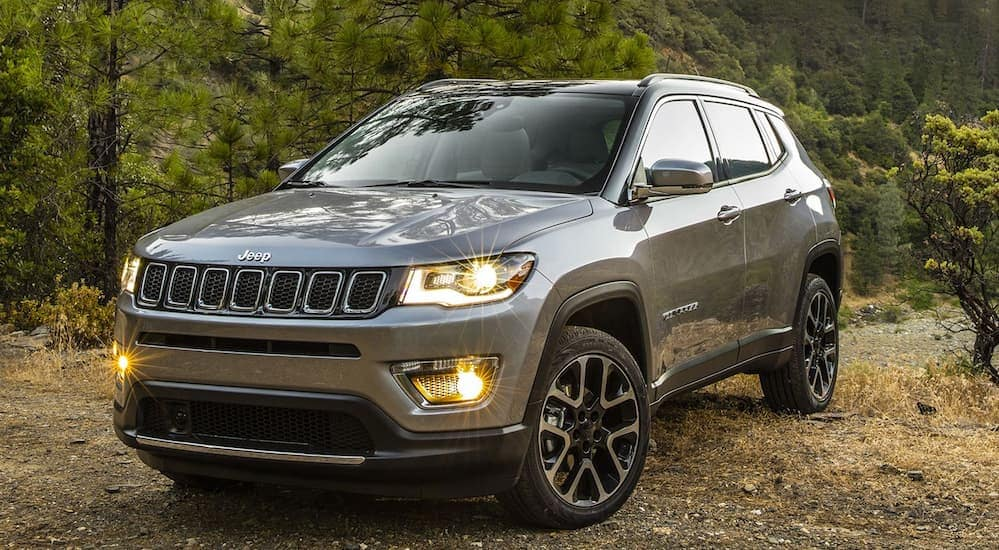 A grey 2020 Jeep Compass is parked on a dirt trail that's overlooking trees.