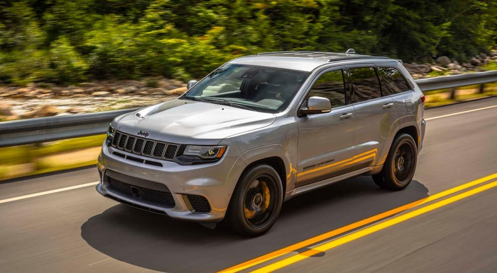 A grey 2020 Jeep Grand Cherokee Trackhawk is driving on a treelined road near Costa Mesa, CA.