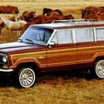 A red and wood-sided 1991 Jeep Grand Wagoneer is parked in a pasture with horses.