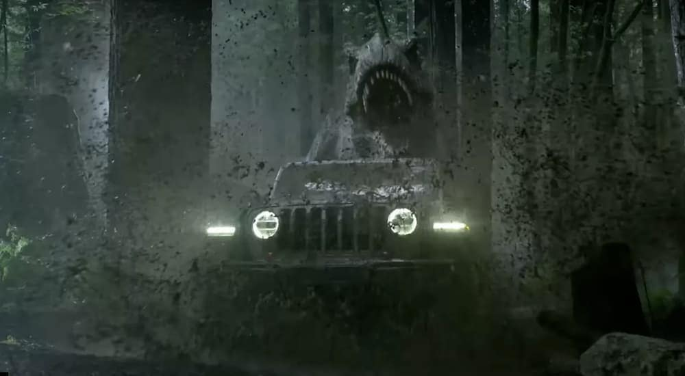 A scene from the Jurassic park Super Bowl commercial shows a T-Rex chasing Jeff Goldblum in a 2018 Jeep Wrangler, which could be found at a used Jeep dealership near me. in Costa Mesa, CA