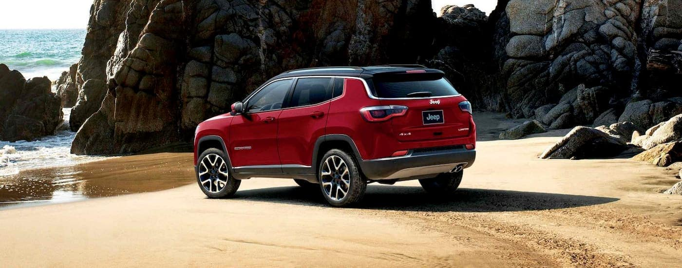A red 2020 Jeep Compass is parked on the shore at the ocean.
