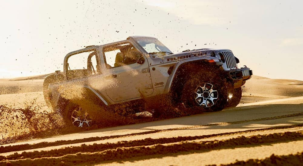 A silver 2020 Jeep Wrangler is driving through the sand at a beach near Costa Mesa, CA.