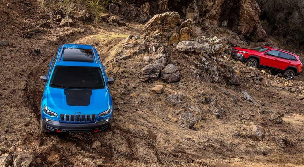 A red 2020 Jeep Cherokee Trailhawk is following a blue one up a tough trail.