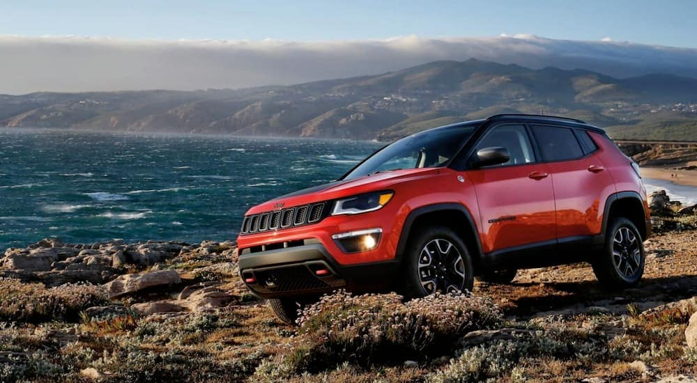 A red 2020 Jeep Compass Trailhawk is on a cliff at the ocean near Costa Mesa, CA.