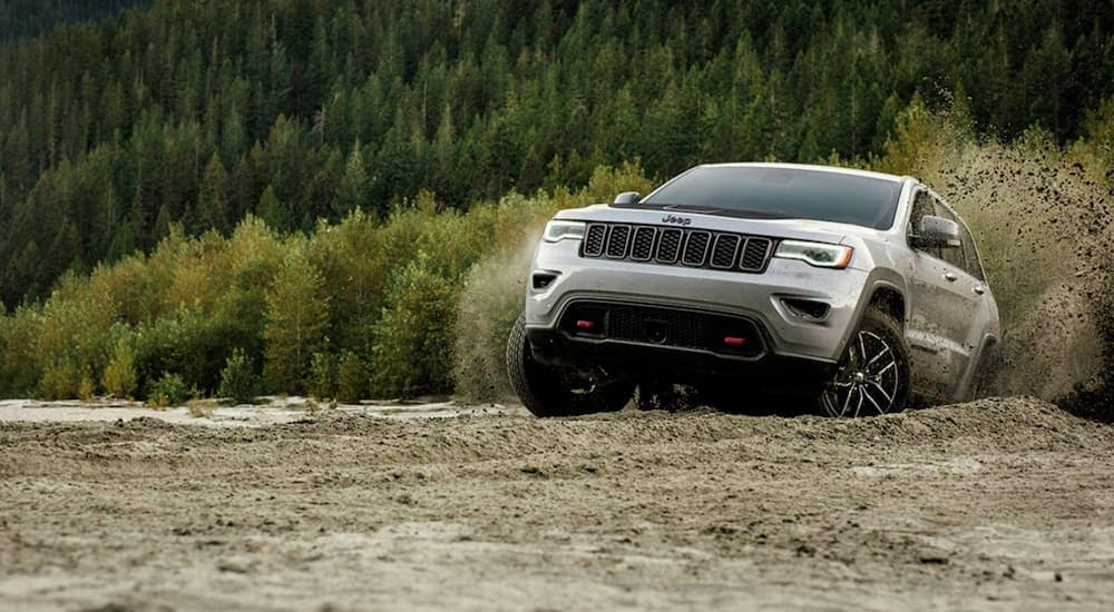 A silver 2020 Jeep Grand Cherokee, which is a popular Jeep for sale, is driving off-road in the dirt.