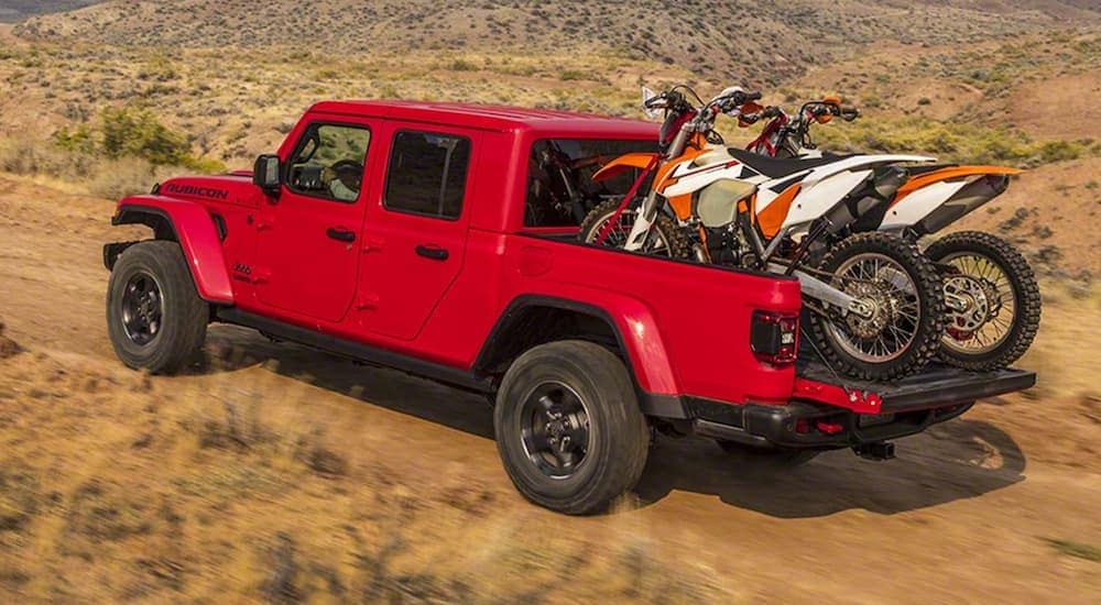 A red 2020 Jeep Gladiator, which is a favorite Jeep for sale in Costa Mesa, CA, is driving on a dirt road with two dirt bikes in the bed.