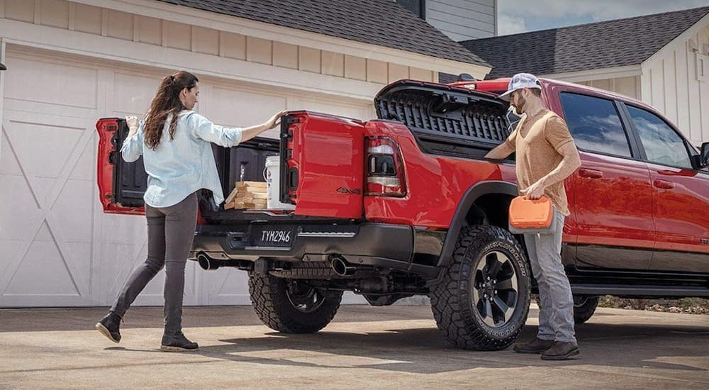 A woman is opening her Ram 1500's Multifunction Tailgate to unload building equipment.