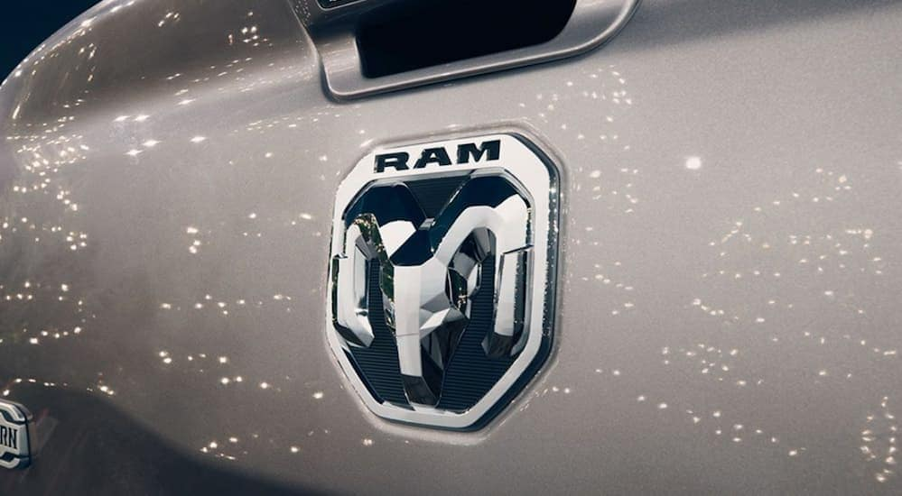 A close up of the Ram logo on a silver tailgate is shown with lights shining on it.