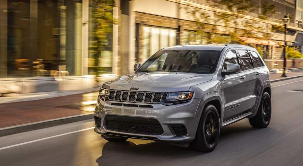 A grey 2020 Jeep Grand Cherokee Trackhawk is driving on a city street past blurred buildings near Costa Mesa, CA.
