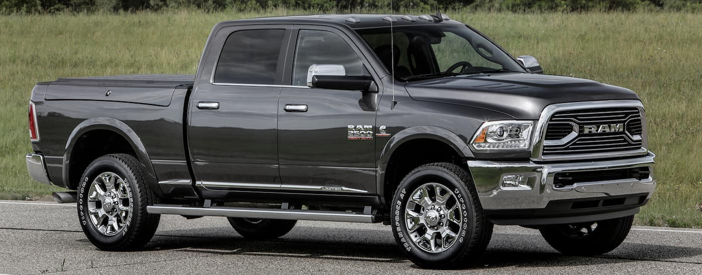 A grey 2016 Ram 2500 is driving on a grass-lined road.