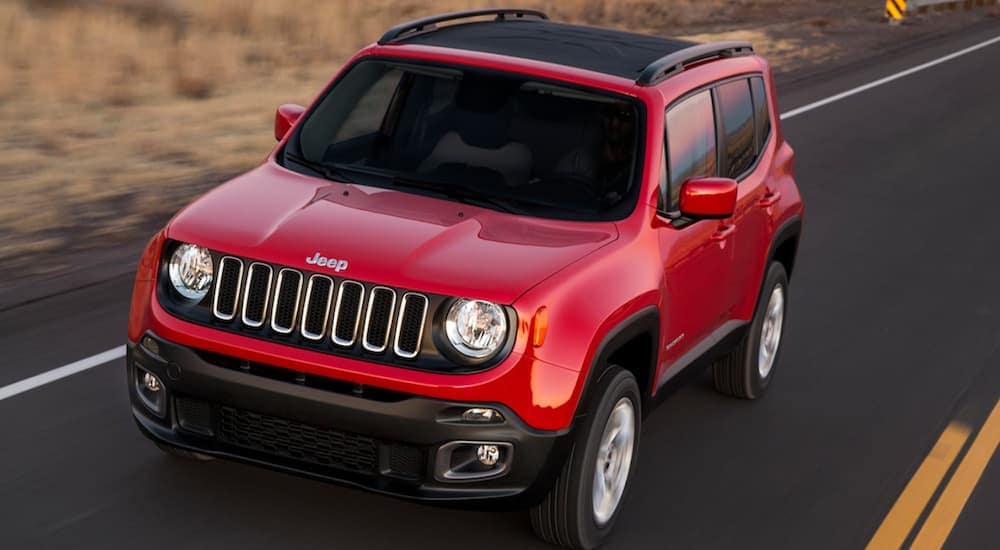 A red 2018 Jeep Renegade, which is a popular option among used cars for sale, is driving on a highway past brown grass at dusk.