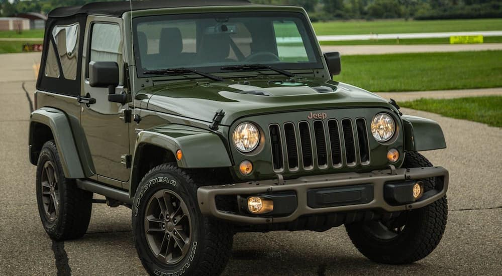 A green 2016 Jeep Wrangler is parked in an empty parking lot near Costa Mesa, CA.