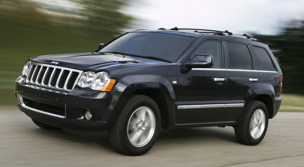 A black 2010 Jeep Grand Cherokee, a popular vehicle that you can find priced under 10k, is driving past blurred trees near Costa Mesa, CA.