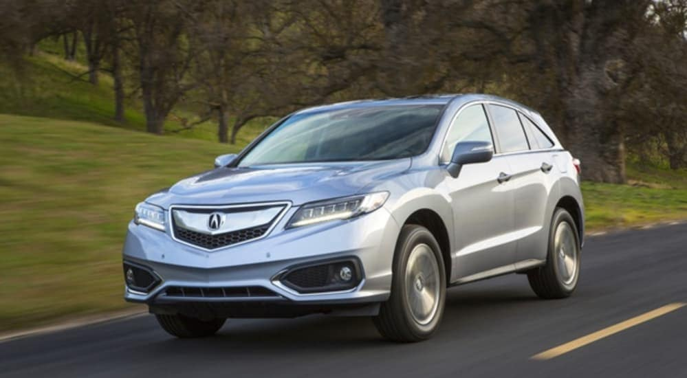 A silver 2016 Acura RDX is driving on a tree lined road.