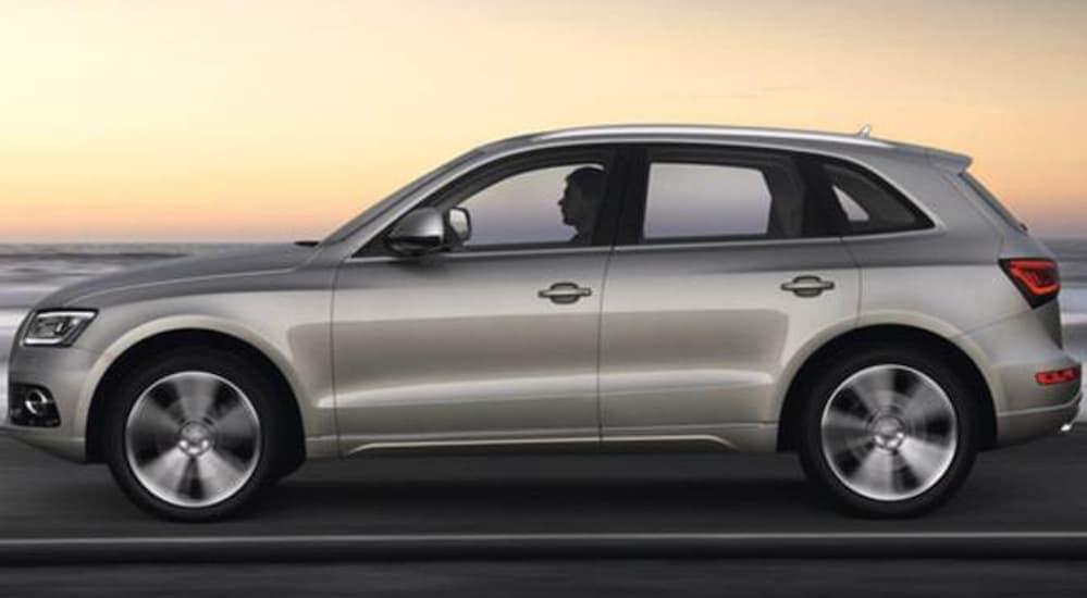 A side view of a gold 2016 Audi Q5 is shown while driving next to the ocean.