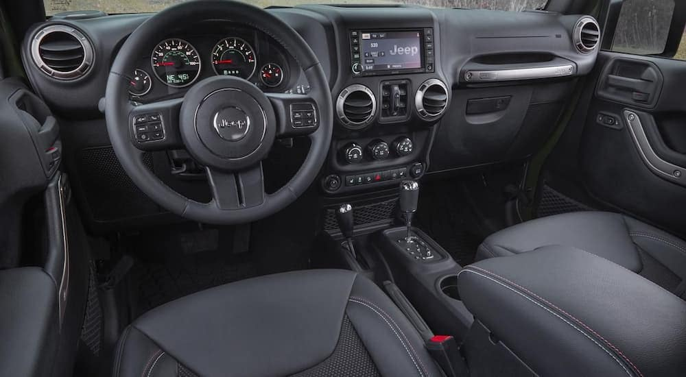 The front black interior of a 2016 Jeep Wrangler is shown with a UConnect system.