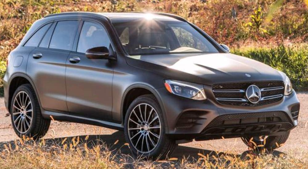 A grey 2016 Mercedes-Benz GLC is parked next to a field near Costa Mesa, CA.