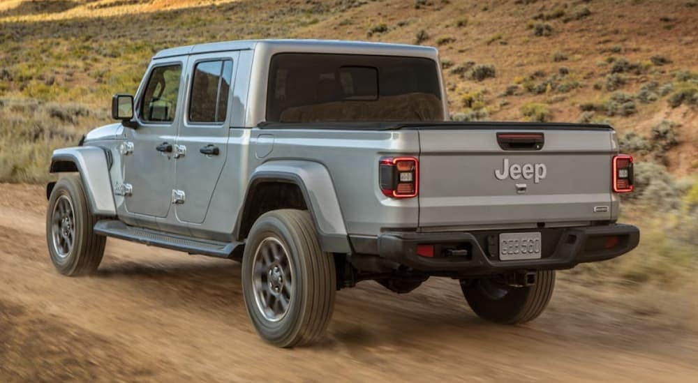 A silver 2020 Jeep Gladiator is driving on a dirt trail.