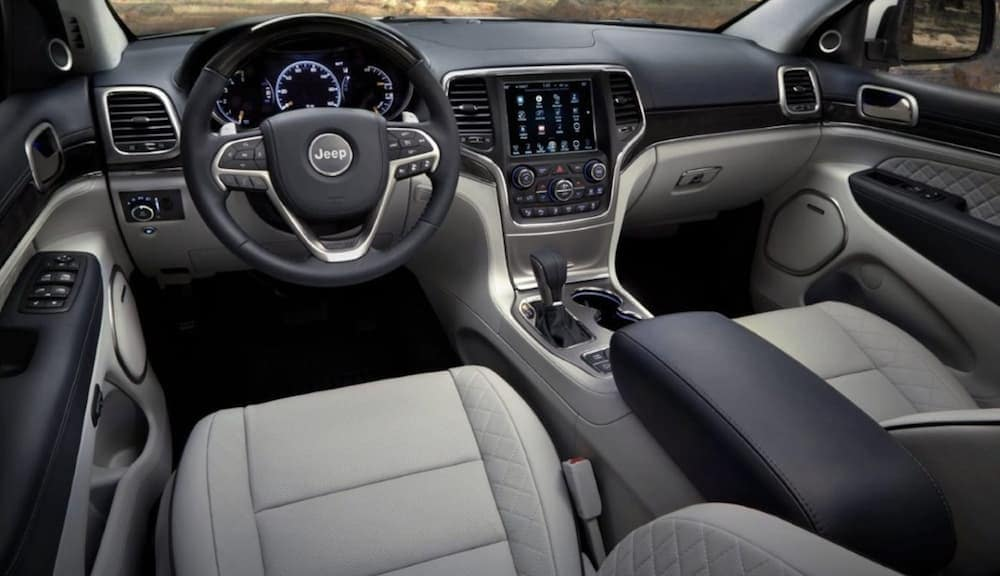 The front white and black leather interior of a 2020 Jeep Grand Cherokee Summit is shown.