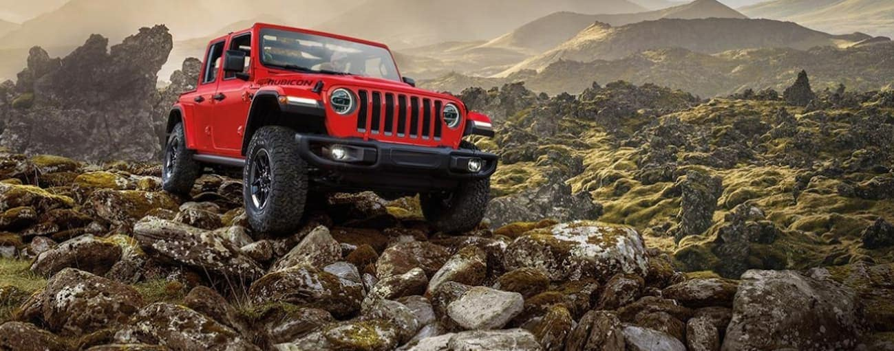 A red 2020 Jeep Wrangler is off-roading on rocks in front of mountains.