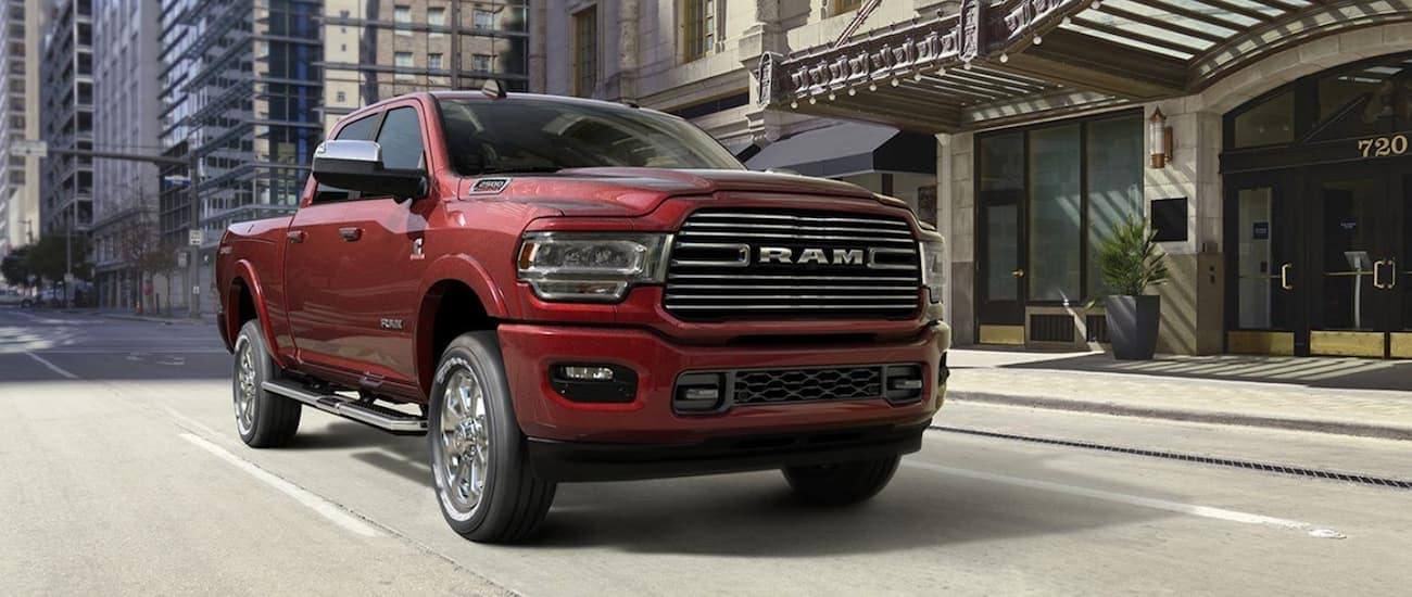 A red 2020 Ram 2500 is driving on a city street near Costa Mesa, CA.