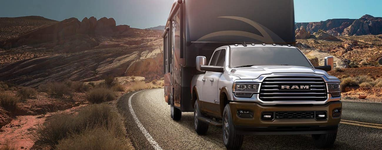 A white 2020 Ram 2500 is towing a large RV trailer through the desert.