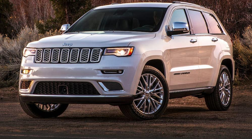 A white 2020 jeep Grand Cherokee is parked on a dirt trail near Costa Mesa, CA, at dusk.