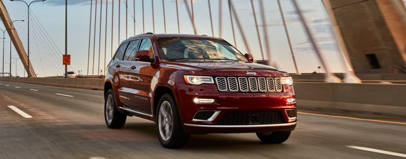 A red 2020 Jeep Grand Cherokee Laredo is driving on a bridge at dusk.