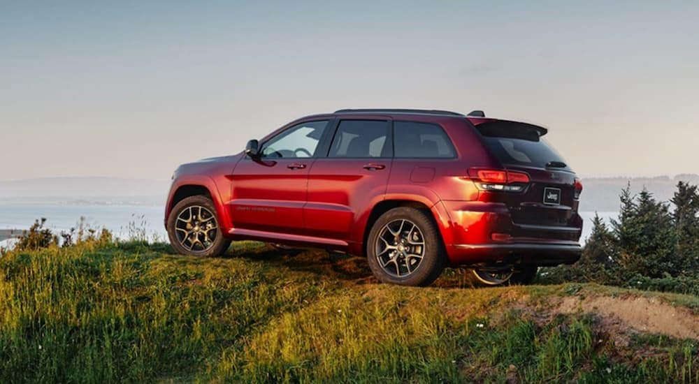 A red 2020 Jeep Grand Cherokee for sale is parked on a hill that's overlooking a beach at dusk.