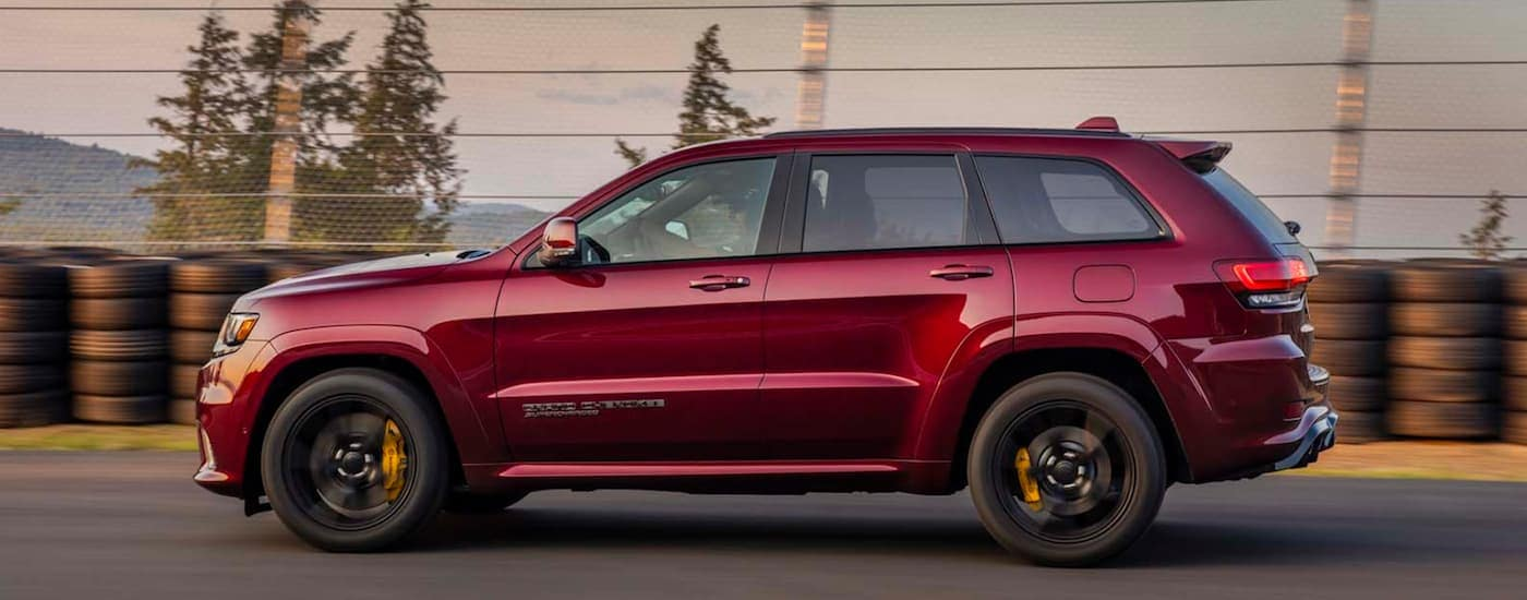 A side view of a red 2020 Jeep Grand Cherokee Trackhawk is driving on a racetrack near Costa Mesa, CA.