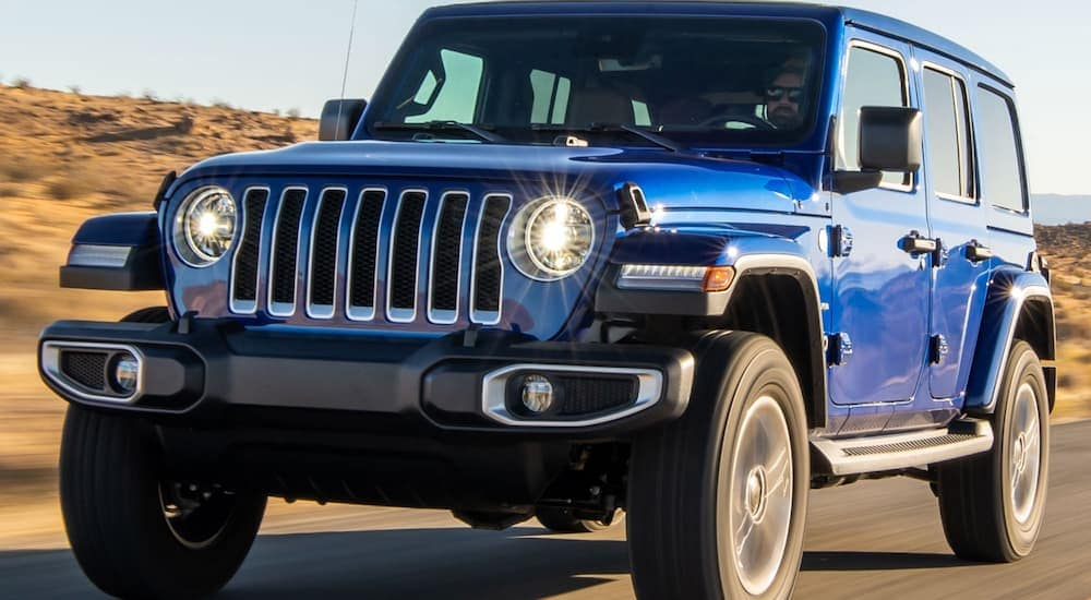 A blue 2020 Jeep Wrangler for sale is driving on a road outside of Costa Mesa, CA.