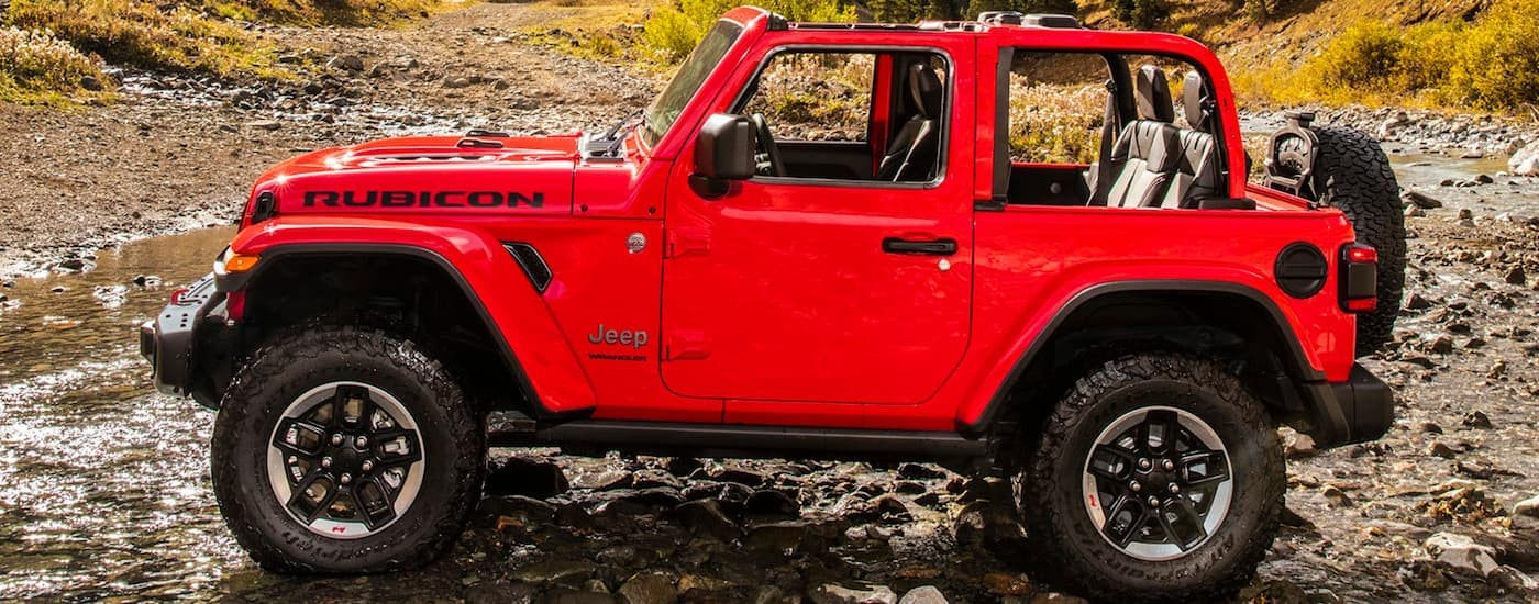 A side view of a red 2020 Jeep Wrangler Rubicon is parked on rocks while off roading near Costa Mesa, CA.