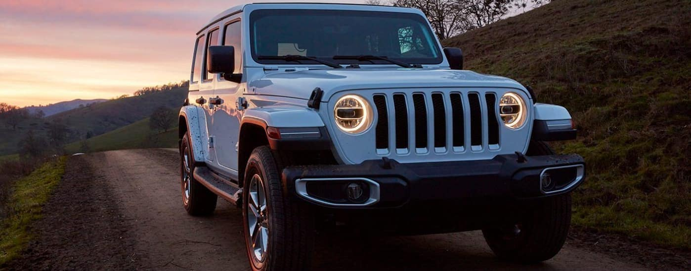 A white 2020 Jeep Wrangler Sport is parked on a dirt road near Costa Mesa, CA, at dusk.