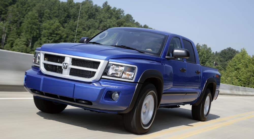 A blue 2011 Dodge Dakota, which is a model you may find used at a Ram dealership in Costa Mesa, CA, is driving on a treelined highway near Costa Mesa, CA.