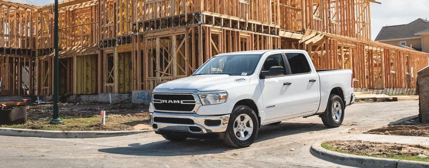 A white 2020 Ram 1500 is leaving a house under construction.