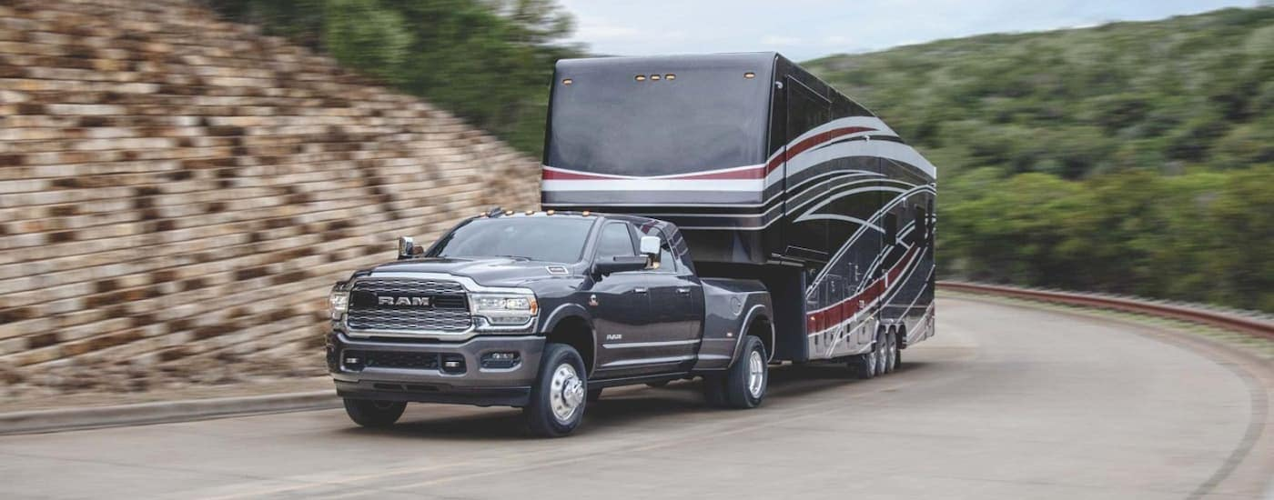 A black 2020 Ram 3500 is towing a large trailer uphill.